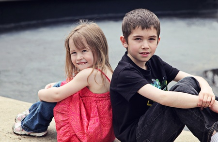 Boy and Girl posing on stone outside in spring photo