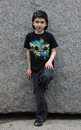 Boy posing on stone wall outside in spring photo