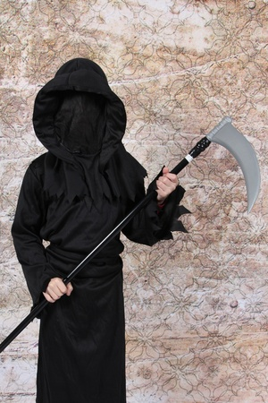 grim reaper: Boy in Halloween Suit with weapon in hand Stock Photo