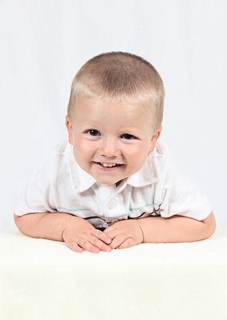 trusting: Little boy posing with smile on white