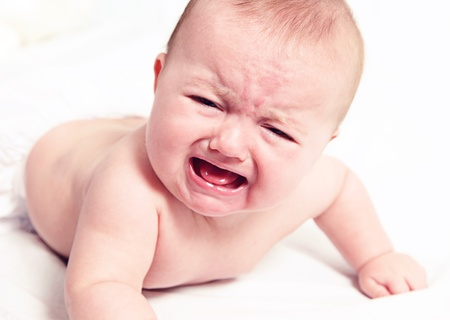 baby crawling: Little baby girl crying on white blanket Stock Photo
