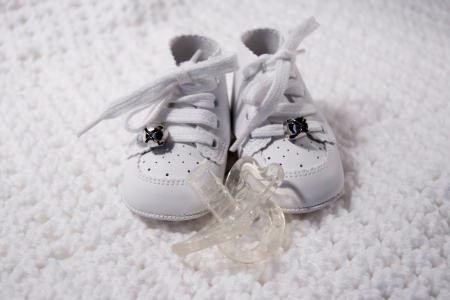 Pair of Babies first shoes with pacifier photo