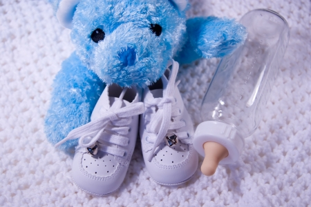 baby's feet: Pair of Babies shoes with Teddy Bear and Bottle