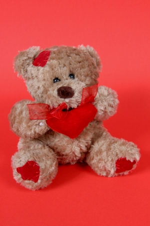 Brown Teddy Bear with hearts on red background photo