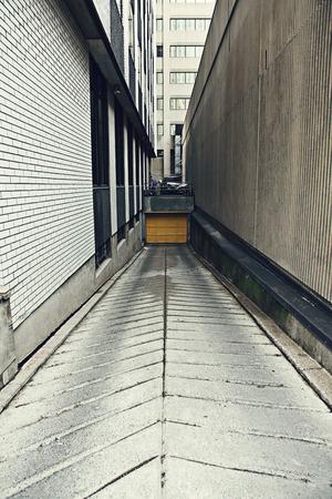 Concrete alleyway in city with door between two buildings photo