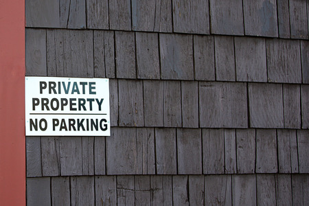 property: Private Property No Parking sign on brown wooden wall