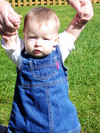 generration: Little Baby Girl in jean dress learning to walk