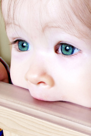 generration: Little Baby biting on crib, taken closeup with green eyes