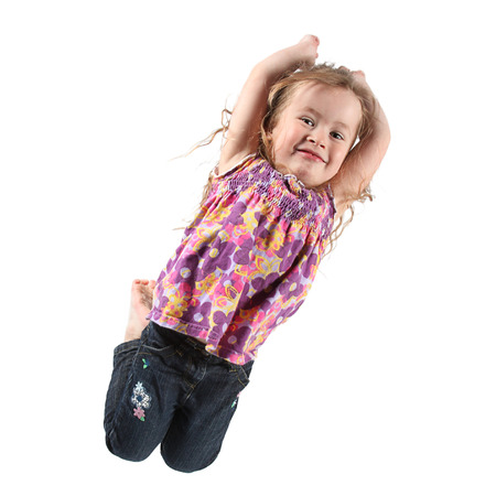 Beautiful Little Girl Jumping for Camera in Studio photo