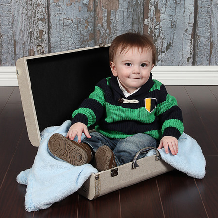 Young boy sitting in suitcase photo
