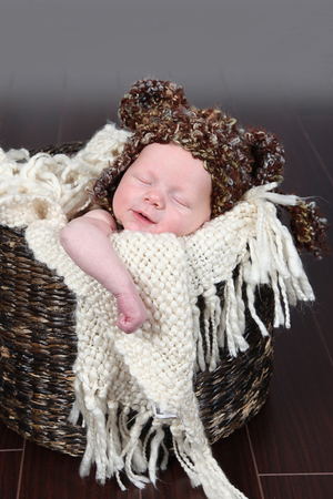 Adorable baby sleeping in basket with cute hat
