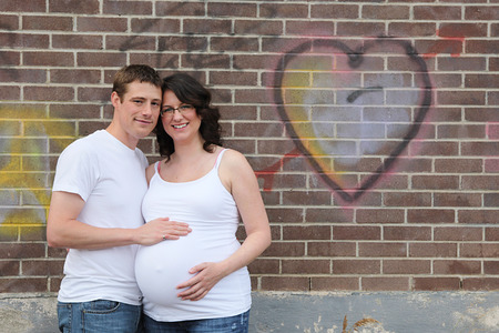 4 months belly: Maternity photos of a woman with brink wall as a background - 8 months pregnant Stock Photo