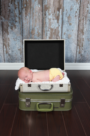 Cute baby sleeping in suitcare bed