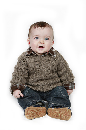 sitting on the ground: Young boy sitting on the ground