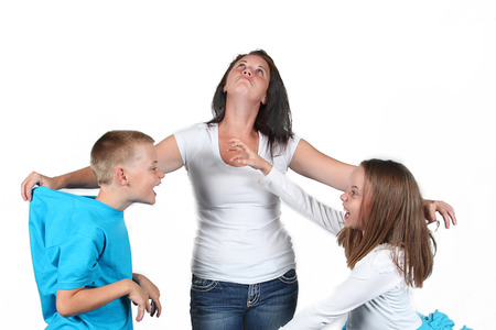 Mother holding two kids as they fight with each other.