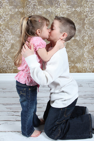 Adorable little brother and Sister kissing on studio background
