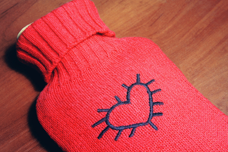 warmer: Red stylish warmer with heart on it on wooden background
