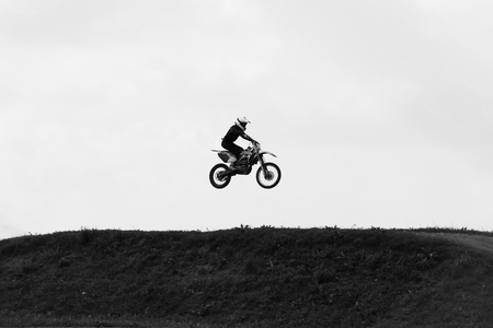 scrambler: Motorbike jumping in the sky on hide speed black and white photo