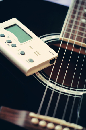 Guitar and tuner for toning musical instruments Reklamní fotografie - 62918656
