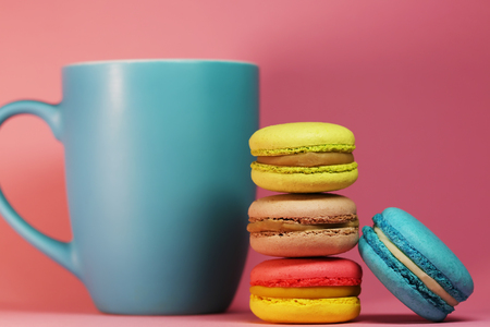 Blue tea cup on pink background with macaroons