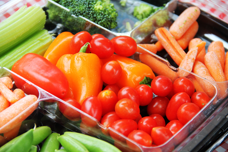 Assorted vegetables like tomatos and carrot in plastic container