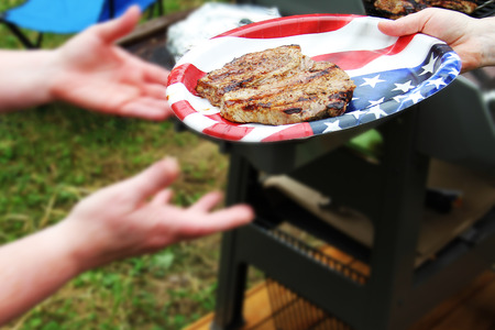Beef steak on plastic plate with american flag close up photo Stock Photo