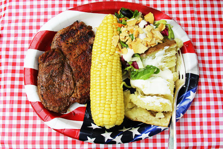 Beef steak, corn, salad and baked potato on papper plate