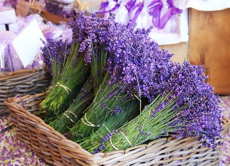Beautiful purple lavender bouquets lie in a wicker basket on the market Stock Photo