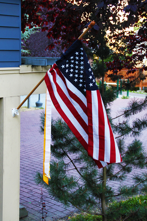 American flag fixed on the building flutters outside Stock Photo