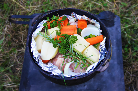 Dish of potato, carrot, onion, chicken and herbs in pot redy to be cooked
