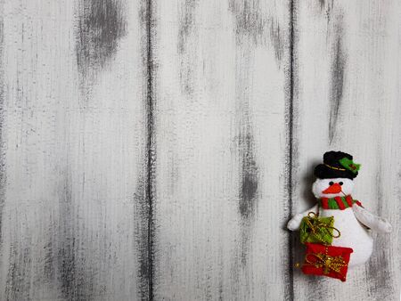 Handmade bauble figurines a snowman. Christmas felt decoration on a white wooden background. Holiday background with a copy space. Stock fotó
