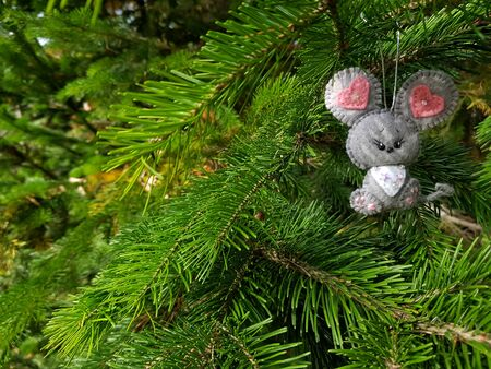 Christmas felt decoration on a spruce branch. Handmade bauble figurines symbol of the year - mouse. Holiday background with a copy space.