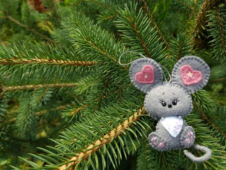 Christmas felt decoration on a spruce branch. Handmade bauble figurines symbol of the year - rat. Holiday background with a copy space.