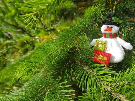 Christmas felt decoration on a spruce branch. Handmade bauble figurines of snowman. Holiday background with a copy space. Stock fotó