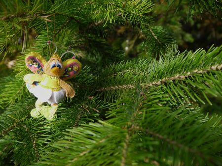 Christmas felt decoration on a spruce branch. Handmade bauble figurines a butterfly. Holiday background with a copy space.