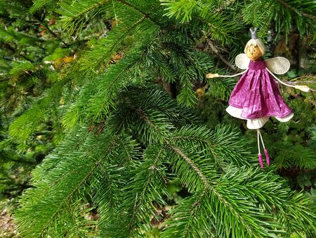 Pink vintage bauble figurines of princess. Christmas sparkle decoration on a spruce branch. Holiday background with a copy space. Stockfoto