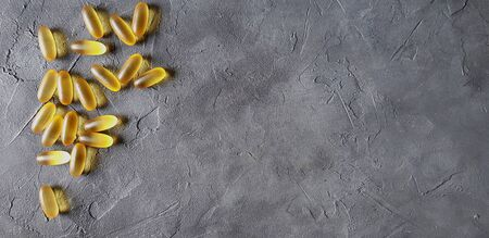 Transparent matte yellow gel capsules of omega and fish oil on a gray concrete background. The concept of a healthy lifestyle, the treatment of dietary supplements, naturopathy and alternative medicine. Horizontal photo.