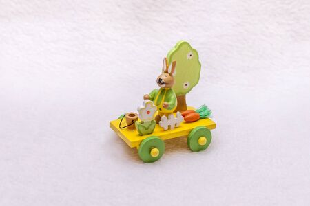 Easter train and a rabbit with carrots, a bucket, a tree, a fence and spring flowers - a wooden transport toy, yellow, green and orange colors, a platform with wheels from the trailer. Photo with copy space