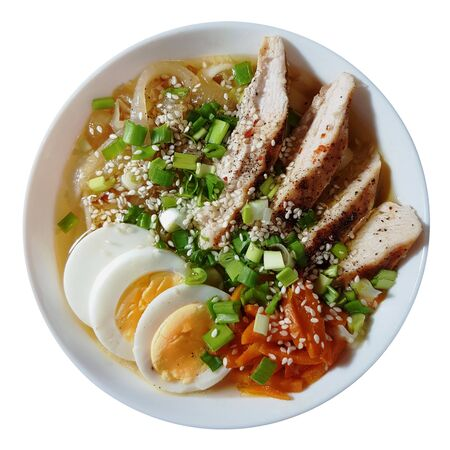 Ramen noodles soup with chicken, eggs, carrots, onions in a golden miso broth. A hot, hearty Japanese dish. Photo isolated on white background