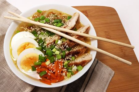 Ramen noodle soup with chicken, eggs, carrots, onions in miso broth. A plate on a wooden stand, next to a toweling towel. Hot, hearty Japanese dish. Stock photo horizontal Stok Fotoğraf