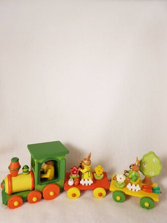 Easter rabbits bunny on train with an eggs, carrots, a bucket and spring tree and flowers, a white fence - cute wooden transport toy, of orange, yellow, red and green. Vertical photo with copy space