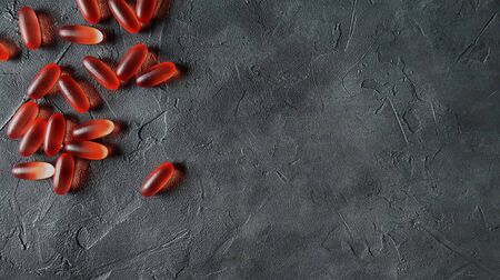 Transparent matte red gel capsules of vitamin and oil on a gray concrete background.