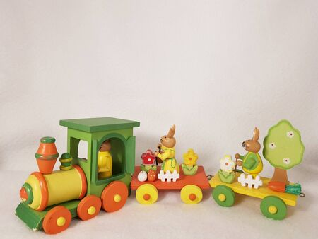 Happy Easter rabbits bunny on train with an eggs, carrots, a bucket and spring tree and flowers, a white fence - cute wooden transport toy, of orange, yellow, red and green. Photo with copy space