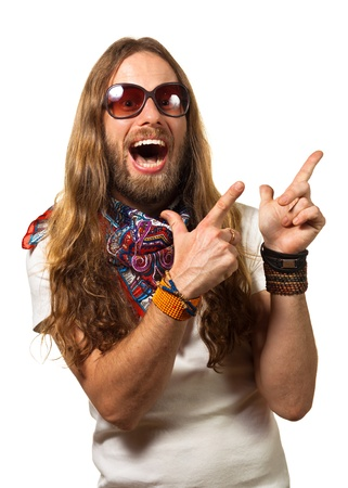 Groovy and happy young man dressed like a hippie pointing at copyspace  Isolated on white  Standard-Bild
