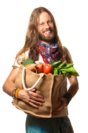 Smiling hippie man holding a bag of fresh, organic fruit and vegetables looking into the camera. Isolated on white.