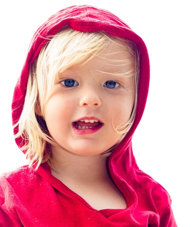 Close-up portrait of a cute young boy in red at the beach isolated on white
