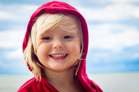 Close-up portrait of a cute, smiling young boy at the beach photo
