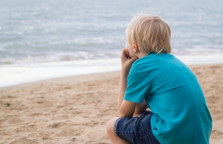 Portrait of a lonely boy at the beach with copy-space. Standard-Bild