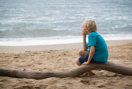 Portrait of a young sad boy thinking on the beach with copy-space. Standard-Bild