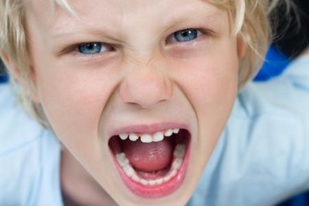 非常に怒っている叫ぶ少年のクローズ アップの肖像画